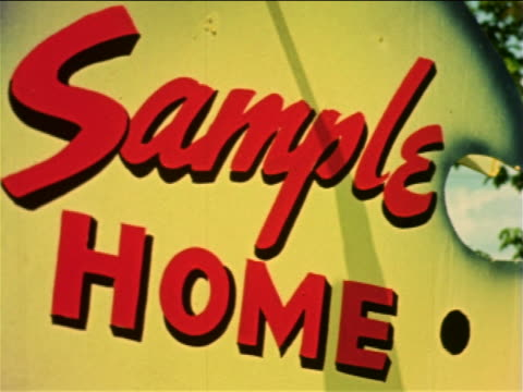 """1959 close up yellow sign with red lettering """"sample home"""" / philadelphia, pa / documentary - 不動産の看板点の映像素材/bロール"""