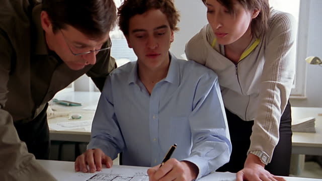Close up young architect discussing blueprints with coworkers in office