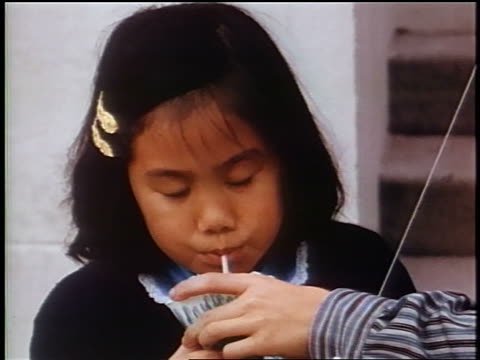 1958 close up young asian girl drinking from cup thru straw / second person holding cup / newsreel - straw stock videos & royalty-free footage