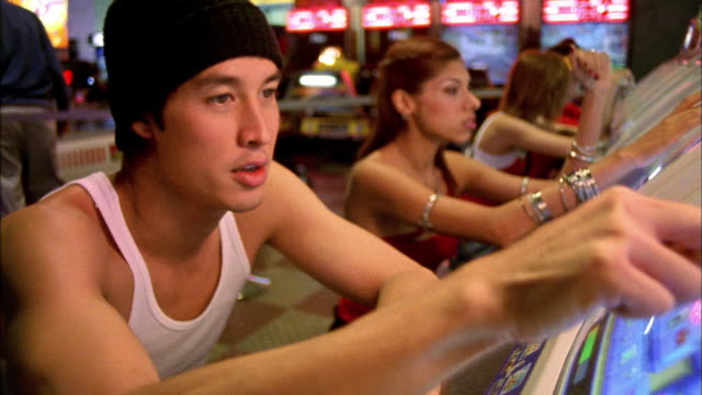 Close up young Asian man playing video games in arcade