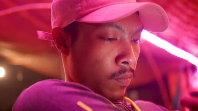 närbild av ung asiatisk man använder mobiltelefon pekskärm i café. - visuellt hjälpmedel bildbanksvideor och videomaterial från bakom kulisserna