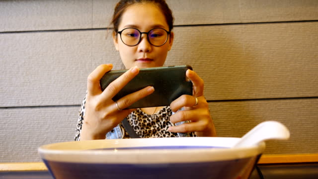 Close up Young Asian woman using mobile phone touchscreen eating Japanese noodle.