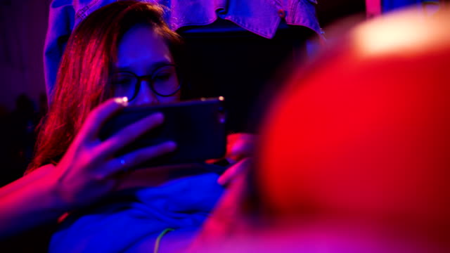 Close up Young Asian woman using mobile phone touchscreen playing game in the room with pink and blue light.