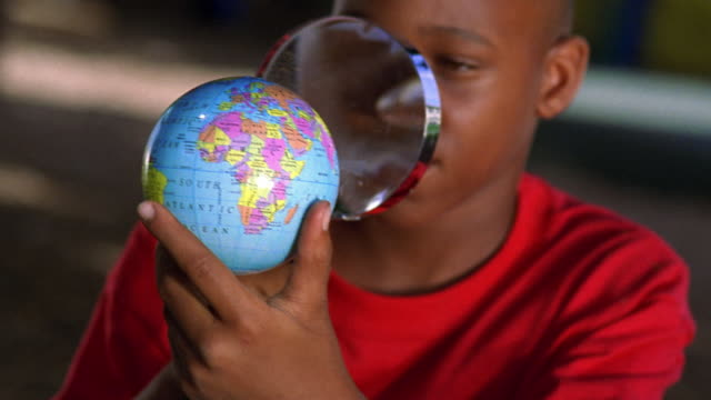 close up young Black boy examining small globe with magnifying glass outdoors