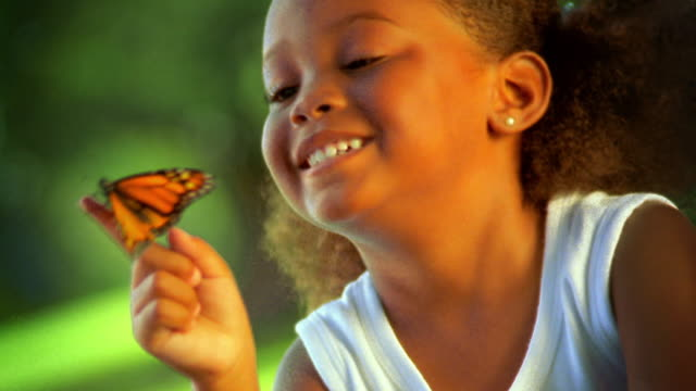 close up young Black girl smiling + looking at monarch butterfly on finger / Florida
