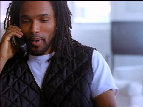 close up young black man with dreadlocks talks + smiles on cordless telephone
