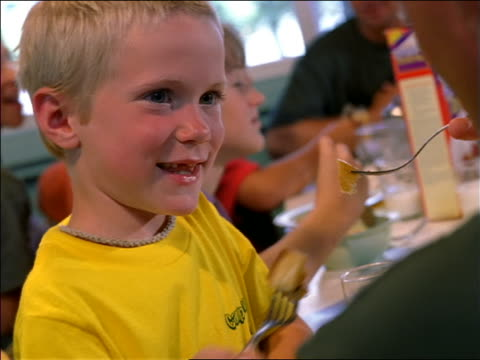 close up young blonde boy eating + smiling at table with others in camp mess hall / hand trying to feed him - 断る点の映像素材/bロール