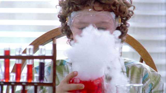 Close up young boy blowing and marveling at dry ice emanating from red liquid in chemistry class