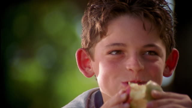Close up young boy eating apple outdoors and smiling at CAM