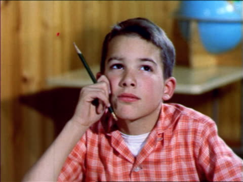 1957 close up young boy holding pencil looking up daydreaming in classroom / new jersey / industrial - 1957 stock-videos und b-roll-filmmaterial