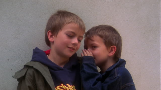 Close up young boy smiling and whispering to boy standing next to him against wall + looking at CAM