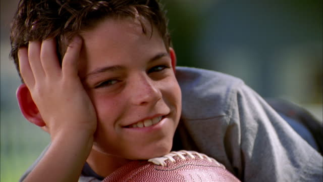 close up young boy smiling at cam outdoors w/his chin resting on football - chin stock videos and b-roll footage