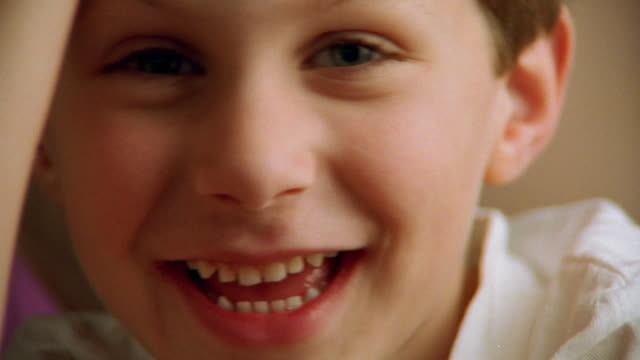close up young boy smiling - solo un bambino maschio video stock e b–roll