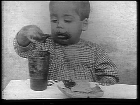 b/w 1921 close up young child with food on face eating messy food out of jar during famine / russia / news - gelatin stock videos and b-roll footage