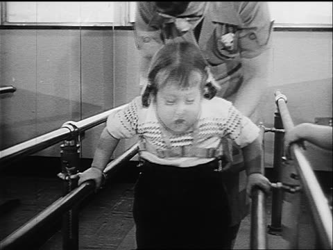 close up young disabled girl with polio using bars to help her walk in physical therapy - 1957 stock videos & royalty-free footage