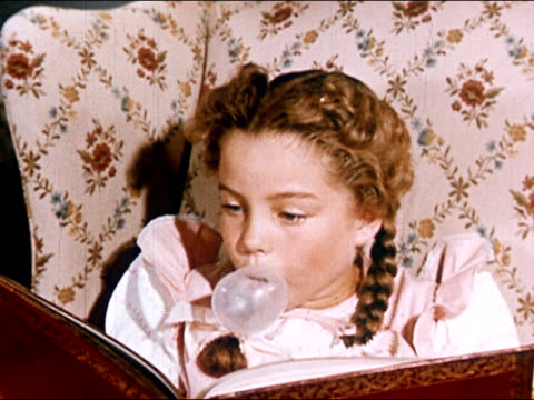 1949 Close up young girl blowing bubble and reading book with surprised look on face/ girl turning head/ AUDIO