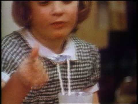 1958 close up young girl eating ice cream + licking spoon / newsreel