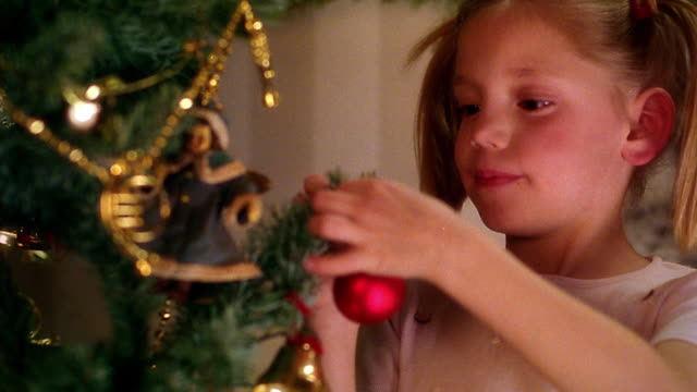 vídeos de stock, filmes e b-roll de close up young girl hanging ornament on christmas tree - ornament