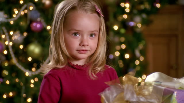 close up young girl holding out wrapped gift and smiling / selective focus christmas tree in background - geschenk stock-videos und b-roll-filmmaterial