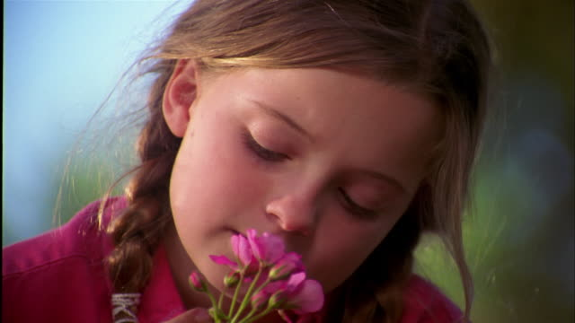 vidéos et rushes de close up young girl holding pink flower and looking at cam - neuf