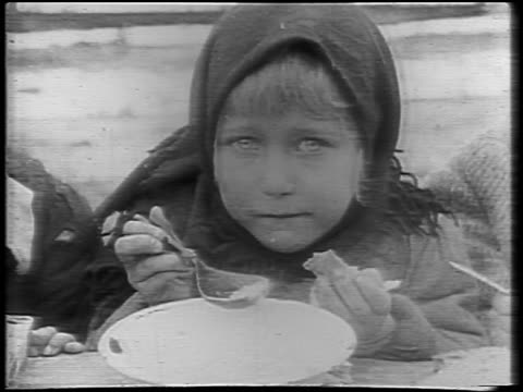 B/W 1921 close up young girl in babushka eating outdoors in Winter / Russia / newsreel