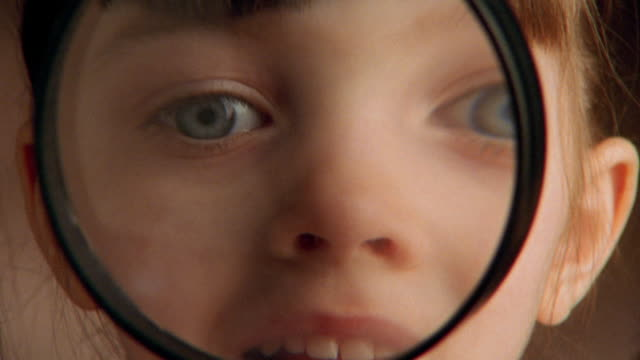 vídeos de stock e filmes b-roll de close up young girl looking through magnifying glass and making faces - lupa