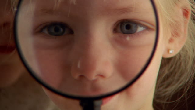 vídeos de stock e filmes b-roll de close up young girl looking through magnifying glass and smiling - lupa