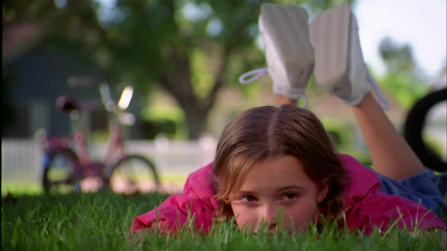 Close up young girl lying on stomach on grass and looking at CAM w/bicycle in background