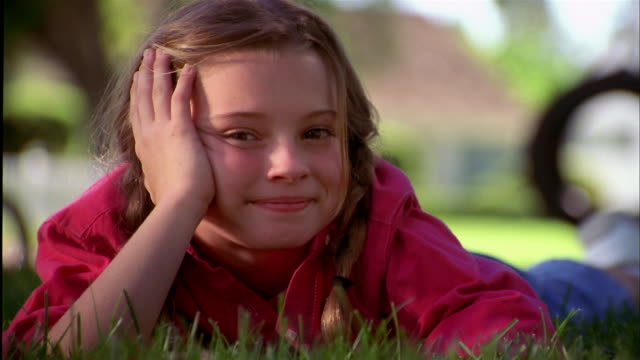 close up young girl lying on stomach on grass and looking at cam / kicking legs in background - reclining stock videos and b-roll footage