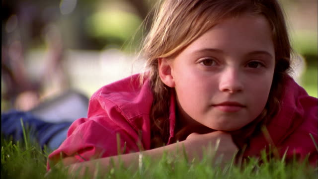close up young girl lying on stomach on grass and smiling at cam - daydreaming stock videos & royalty-free footage