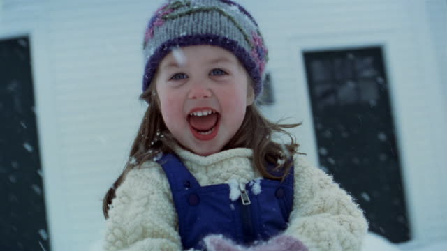 close up young girl playing in the snow / making snowball and throwing it at cam - jumper stock videos and b-roll footage