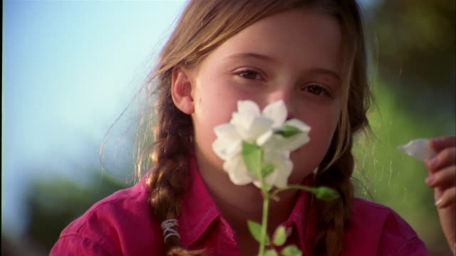 vidéos et rushes de close up young girl smiling and holding white flower toward cam - neuf