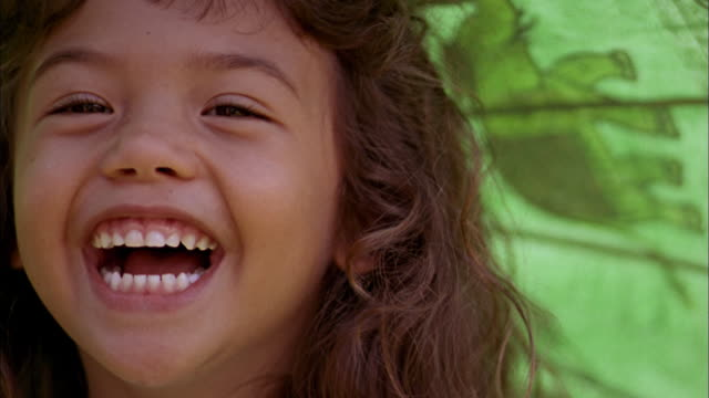close up young girl smiling at cam and holding umbrella - one girl only stock videos & royalty-free footage