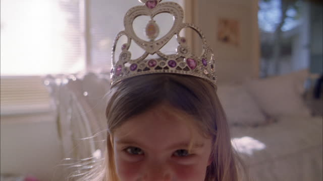 close up young girl smiling at cam and wearing crown - crown headwear stock videos & royalty-free footage