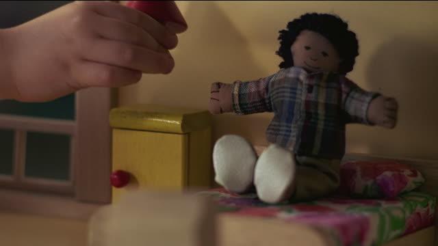 close up young girl's hand putting mini lamp on mini table in dollhouse with doll on mini bed - おもちゃの家点の映像素材/bロール