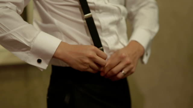 close up young groom dressing suit for wedding day - suspenders stock videos and b-roll footage