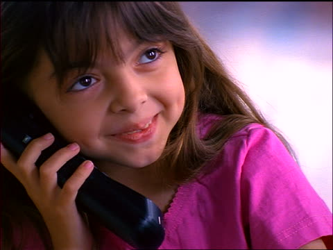 close up young hispanic girl smiles + talks on telephone - landline phone stock videos & royalty-free footage