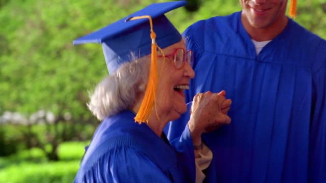 close up pan young hispanic man helping senior woman on stage to receive diploma / all wear caps + gowns - diploma stock videos and b-roll footage