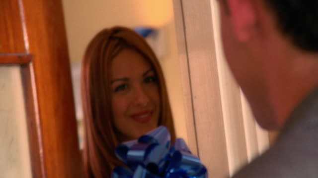 close up young Hispanic woman opening door + looking surprised with man holding gift