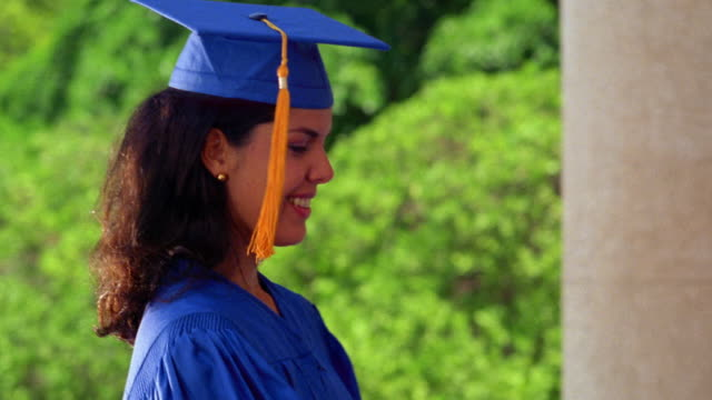 close up pan young hispanic woman receiving diploma from man + adjusting tassle / both wear caps + gowns - diploma stock videos and b-roll footage