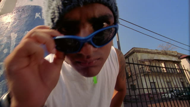 close up young man in knit cap and sunglasses frowning at cam - staring stock videos & royalty-free footage