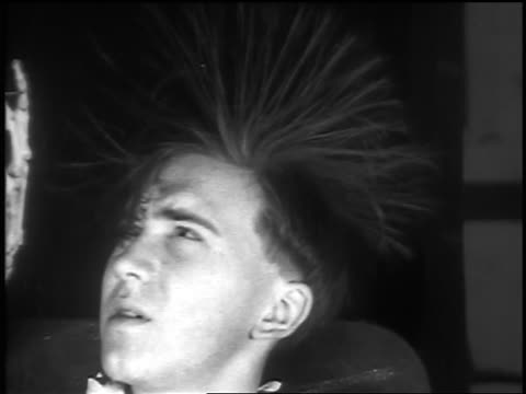 b/w 1936 close up young man with hair standing on end - elettricità video stock e b–roll