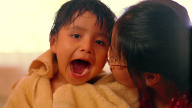 close up young woman kissing native american boy laughing + rubbing his head with towel - タオル点の映像素材/bロール