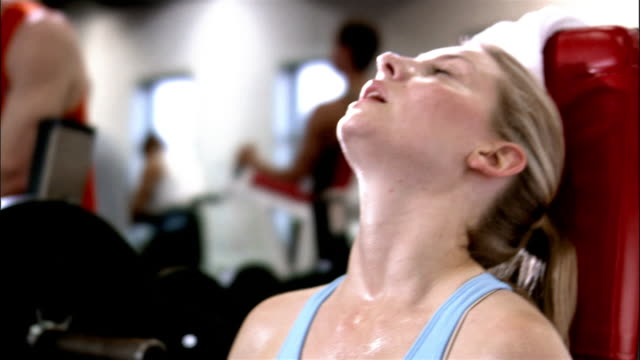 vidéos et rushes de close up young woman lifting weights in health club/ woman looking at camera and smiling - sueur