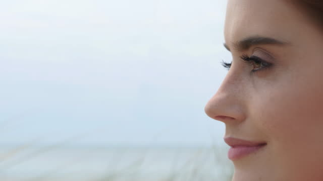 vídeos de stock e filmes b-roll de close up young woman looking at out to sea. - perfil