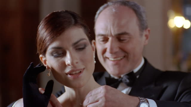 Close up young woman putting on earring / older man giving her pearl choker and putting it on her neck