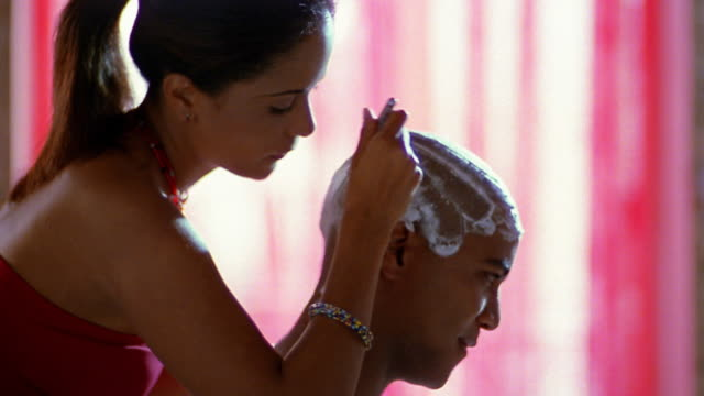 Close up young woman shaving young man's head