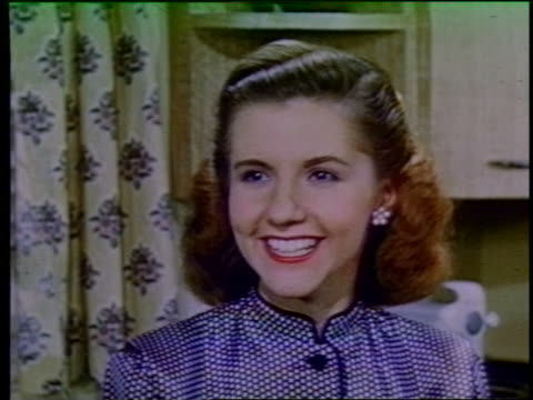 1952 close up young woman smiling + talking indoors