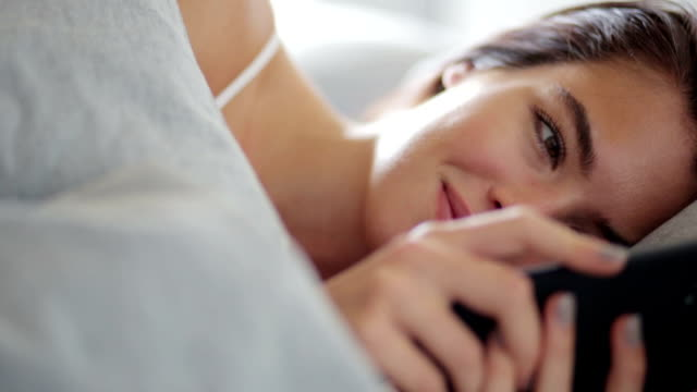 Close up, young woman texting in bed    RO LI