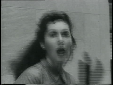 B/W 1961 close up young woman turns to camera with horrified expression